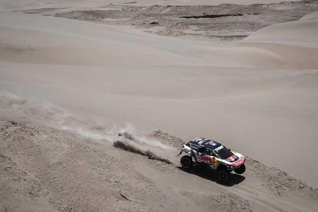Carlos Sainz da las gracias a los cuatro pilotos de moto que le han ayudado a salir de un río seco